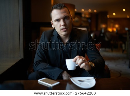 cheerful businessman drinking coffee in a restaurant - stock photo