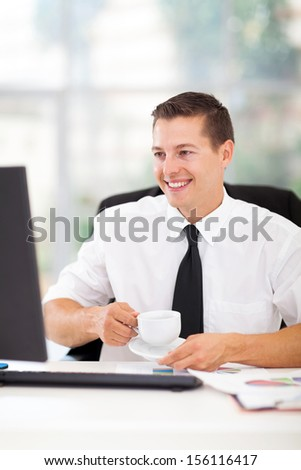 cheerful businessman drinking coffee while working on his computer in office - stock photo