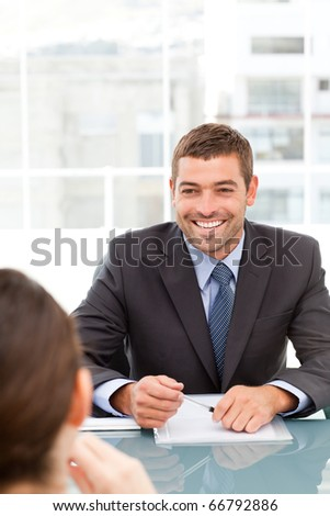 Cheerful businessman during a meeting with a collegue sitting around a table - stock photo
