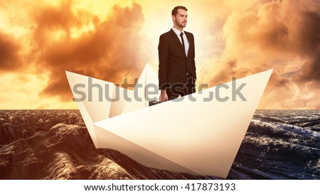 Cheerful businessman holding briefcase while hand in pocket against paper boat floating on the sea - stock photo