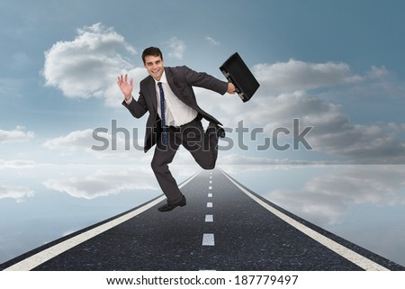 Cheerful businessman in a hurry against road over water reflecting sky - stock photo
