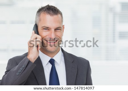 Cheerful businessman in bright office looking at camera while having a phone call  - stock photo