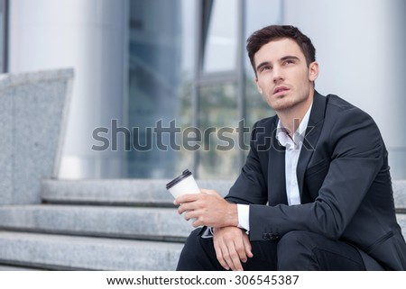 Cheerful businessman is sitting on steps outdoors. He is drinking coffee and relaxing. The man is looking up dreamingly. Copy space in left side - stock photo