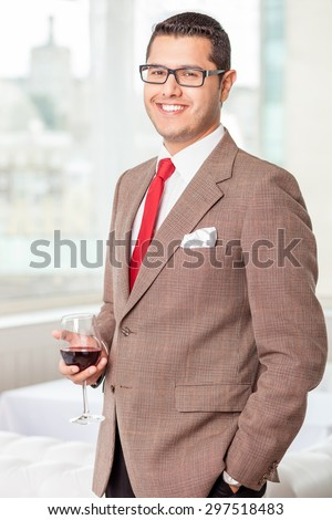 Cheerful businessman is standing and drinking red wine. He is smiling and looking at the camera with happiness - stock photo