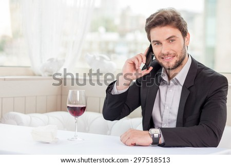 Cheerful businessman is talking on mobile phone in the restaurant. He is arranging a meeting with his client. He is smiling and looking at the camera confidently. Copy space in left side - stock photo
