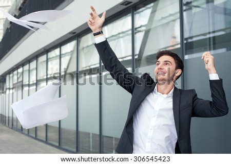 Cheerful businessman is throwing papers with happiness. The deal was done successfully. The man is smiling and gesturing positively - stock photo
