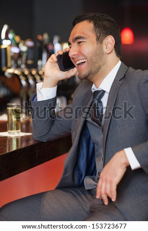 Cheerful businessman on the phone having a drink in a classy bar - stock photo