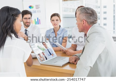 Cheerful businessman posing while his colleagues are working against business team discussing work details - stock photo
