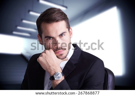 Cheerful businessman posing with hand on chin against grey room - stock photo