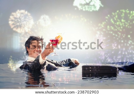 Cheerful businessman relaxing in a swimming pool with a cocktail against colourful fireworks exploding on black background - stock photo