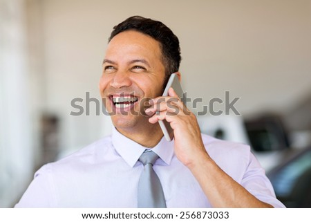 cheerful businessman talking on cell phone - stock photo