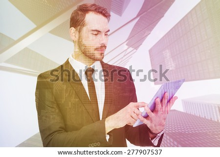 Cheerful businessman touching digital tablet against room with large window looking on city - stock photo