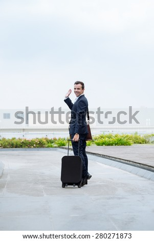 Cheerful businessman with a suitcase waving goodbye and looking at the camera - stock photo
