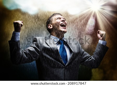 Cheerful businessman with hands up celebrating success - stock photo