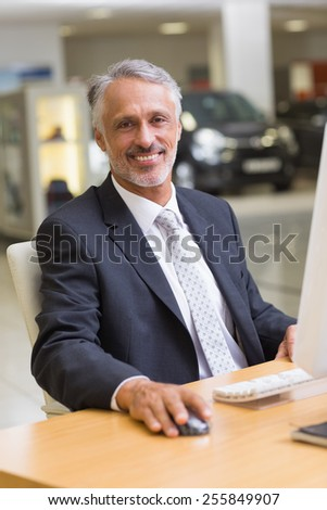 Cheerful businessman working at his desk at new car showroom - stock photo
