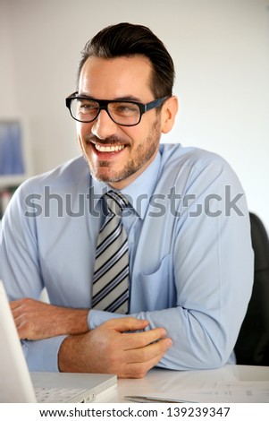 Cheerful businessman working on laptop computer - stock photo