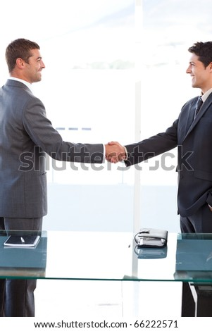 Cheerful businessmen closing a deal by shaking their hands at the office - stock photo