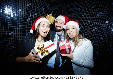 Cheerful businesspeople in Santa caps showing their presents in packages - stock photo
