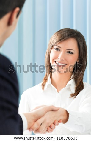 Cheerful businesspeople, or businesswoman and client handshaking - stock photo
