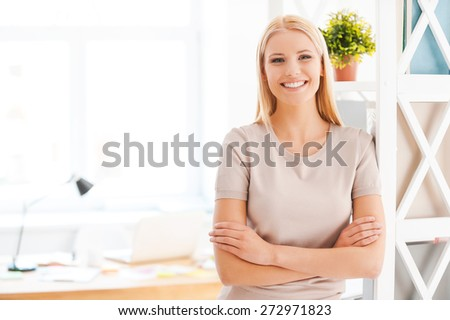 Cheerful businesswoman. Beautiful young woman leaning at the shelf and smiling while standing near her working place in office  - stock photo