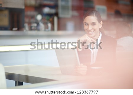 Cheerful businesswoman on a coffee break looking out the window - stock photo