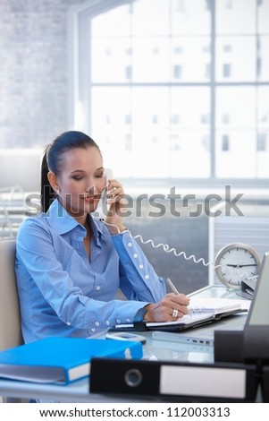 Cheerful businesswoman on landline call, taking notes, smiling. - stock photo