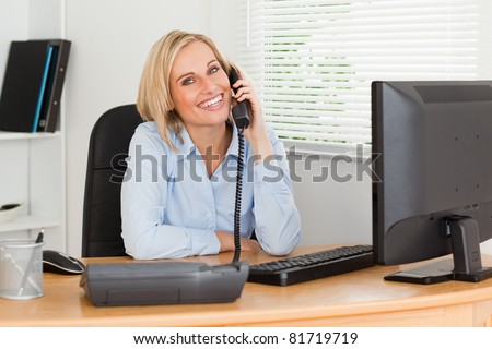 Cheerful businesswoman on phone looking into camera in her office - stock photo