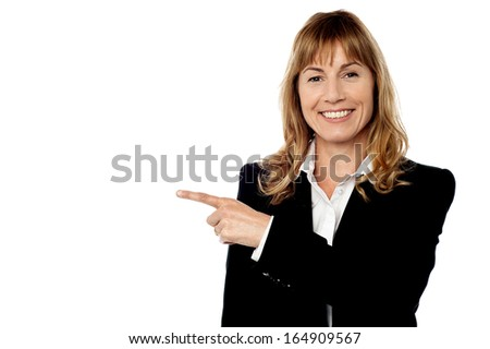 Cheerful businesswoman pointing at something - stock photo