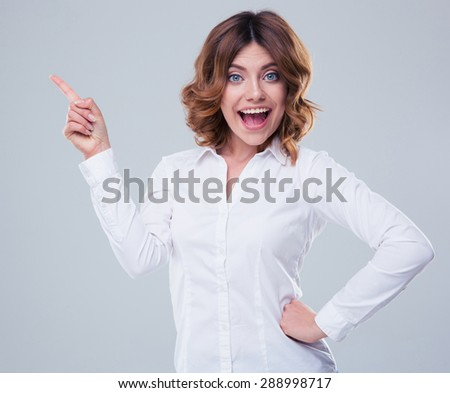 Cheerful businesswoman pointing finger away over gray background - stock photo