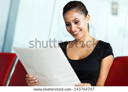 cheerful businesswoman reading newspaper while waiting for her flight at airport - stock photo
