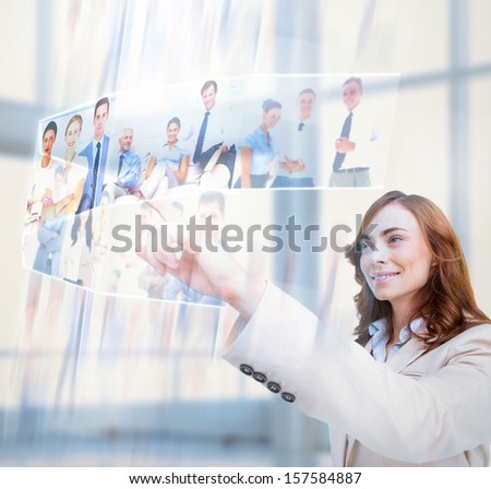 Cheerful businesswoman scrolling pictures on digital screen - stock photo