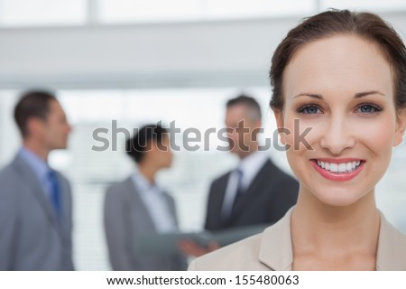 Cheerful businesswoman smiling at camera in bright office - stock photo
