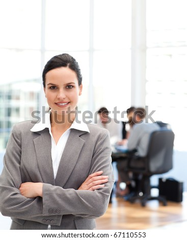 Cheerful businesswoman standing in front of her team while working in the background - stock photo