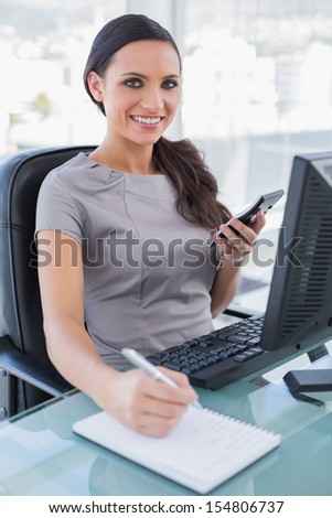 Cheerful businesswoman using calculator and writing in her office - stock photo