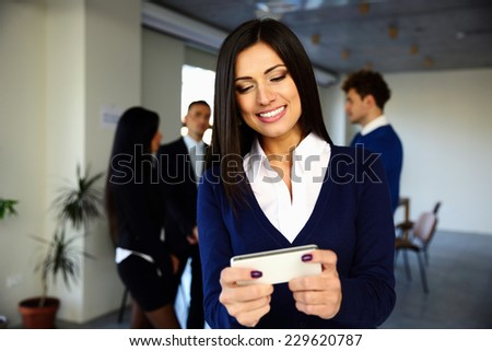 Cheerful businesswoman using smartphone in front of colleagues - stock photo