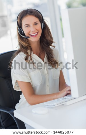 Cheerful businesswoman wearing a headset in her office - stock photo
