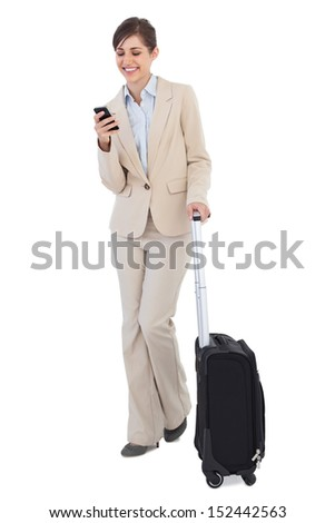 Cheerful businesswoman with suitcase and phone against white background - stock photo