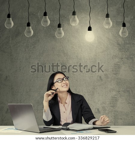 Cheerful businesswoman working with laptop and smiling happy while looking at lightbulb - stock photo