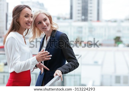 Cheerful businesswomen are standing near the border of building and talking. They are looking forward and smiling. The brunette woman is gesturing with inspiration. Copy space in right side - stock photo