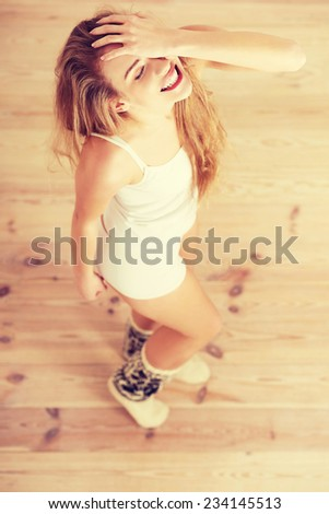Cheerful, carefree young caucasian woman feels happy. Standing, or dacing, posing over wooden floor. - stock photo