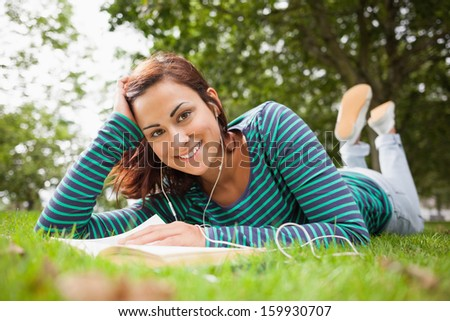 Cheerful casual student lying on grass reading a book on campus at college - stock photo