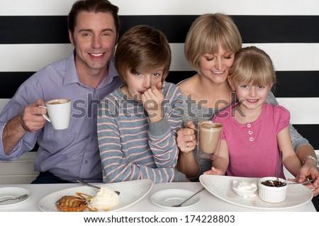 Cheerful caucasian family of four having fun in restaurant - stock photo