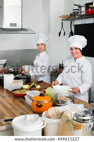 Cheerful charming  smiling female chefs preparing food on restaurant kitchen - stock photo