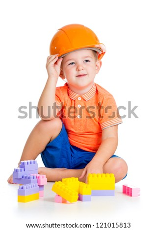 cheerful child boy with hard hat playing with building blocks toys over white background - stock photo