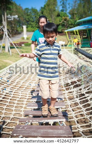 Cheerful child having fun at playground, mother near by. Boy playing at park, outdoors in the day time. Happy asian family on vacation. - stock photo