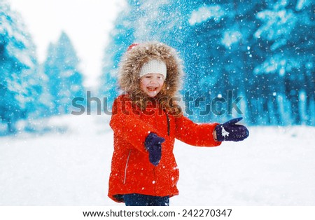 Cheerful child having fun outdoors with snowball in winter snowy day - stock photo