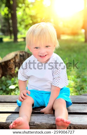 Cheerful Child on the Bench at the Summer Park - stock photo
