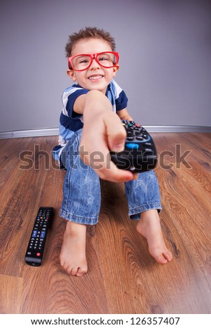 Cheerful child with tv remote control - stock photo
