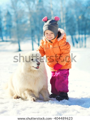 Cheerful child with white Samoyed dog on snow in winter park - stock photo