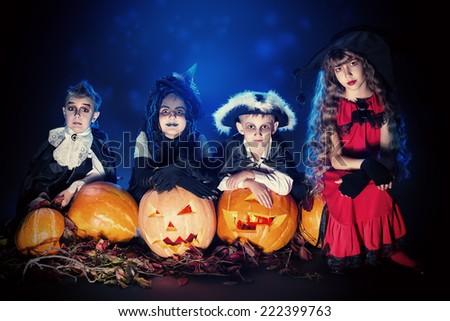 Cheerful children in halloween costumes posing with pumpkin over dark background. - stock photo